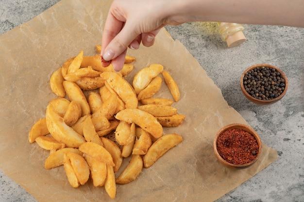 Frauenhand, die pfefferpulver auf gebratene kartoffel auf pergamentpapier setzt.