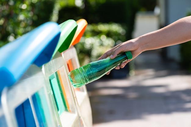 Frauenhand, die plastikflaschenabfall in abfallabfall hält und einsetzt.