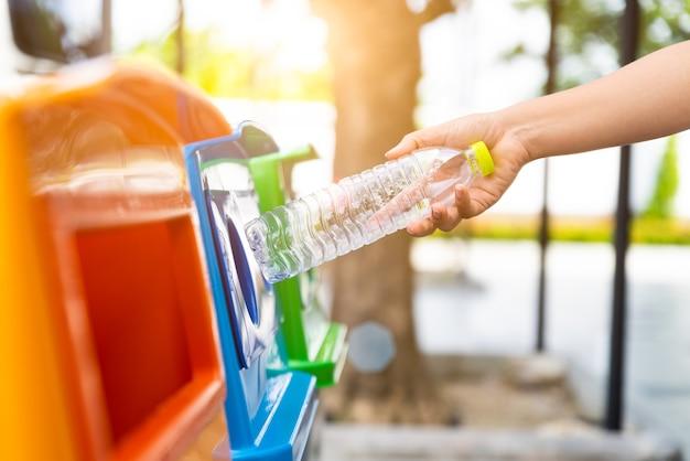 Frauenhand, die plastikflaschenabfall in abfallabfall hält und einsetzt
