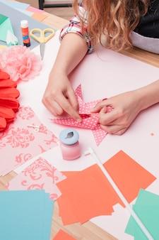 Frauenhand, die polka punktiertes origami feuerrad bildet