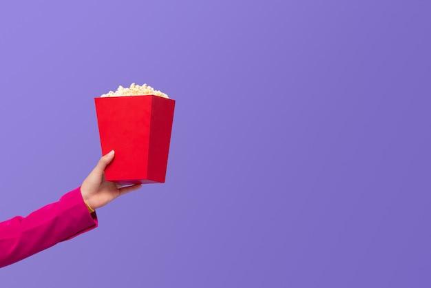 Frauenhand, die popcorn im roten kasten gibt