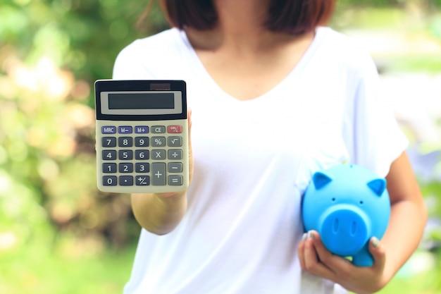 Frauenhand, die rechner und blaues schweinchen auf natürlichem grünem hintergrund, investition und geschäftskonzept hält