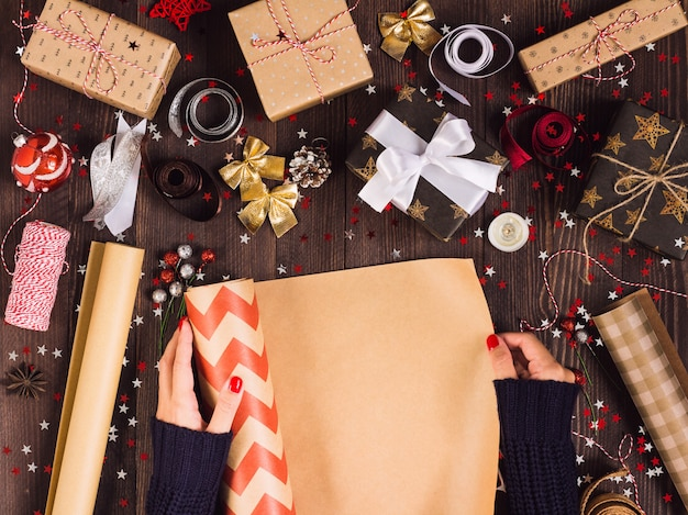 Frauenhand, die rolle des packpapiers für das verpacken der weihnachtsgeschenkbox ausbreitet