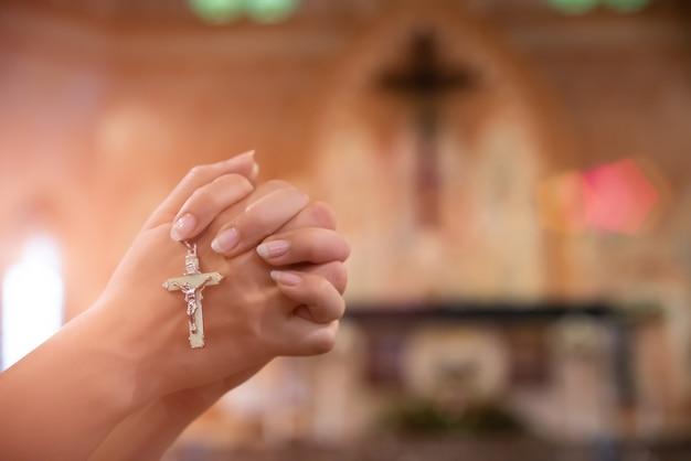 Frauenhand, die rosenbeet gegen kreuz hält und zum gott an der kirche betet