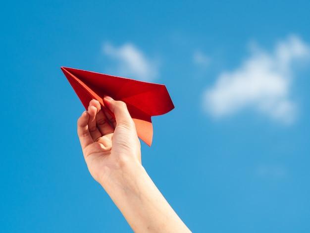 Frauenhand, die rote papierrakete mit hintergrund des blauen himmels hält. freiheitskonzept