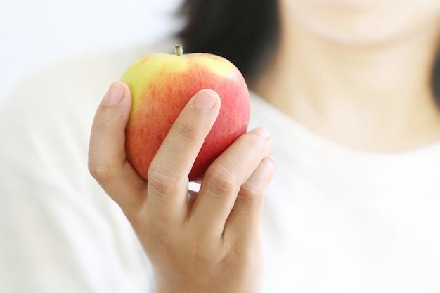 Frauenhand, die roten apfel anhält.