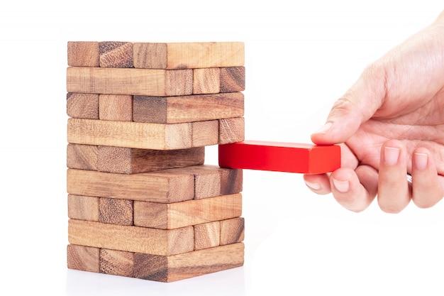 Frauenhand, die roten block von staplungsholzklotz hält. konzept der führung, teamarbeit und anders.