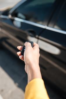 Frauenhand, die schlüssel hält und tür ihres autos schließt