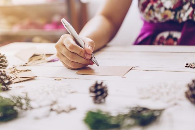 Frauenhand, die schöne weihnachtskarte am tisch schreibt
