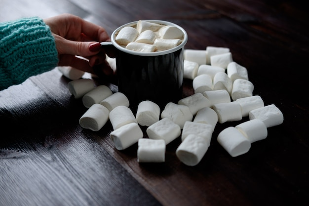 Frauenhand, die schwarze tasse kaffee mit marshmallows unter marshmallows auf hölzerner dunkler oberfläche hält