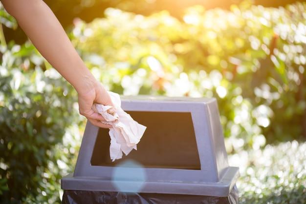 Frauenhand, die seidenpapierabfall in abfallabfall hält und setzt.