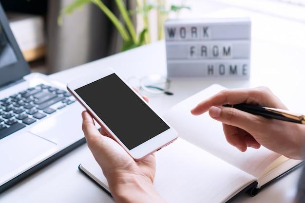 Frauenhand, die smartphone auf weißem schreibtisch mit tagebuch, computer-laptop, brille und arbeit von zu hause wort auf leuchtkasten verwendet.