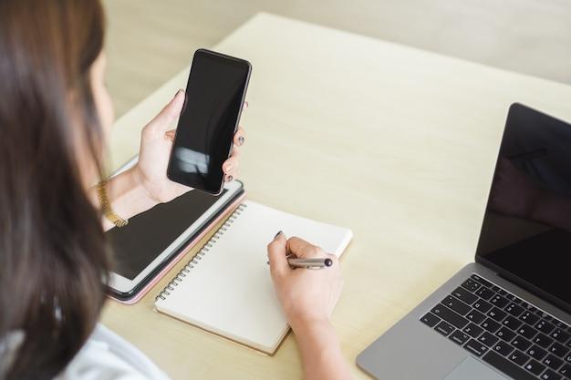 Frauenhand, die smartphone des leeren bildschirms mit laptop und digitaler tablette auf tabelle hält.