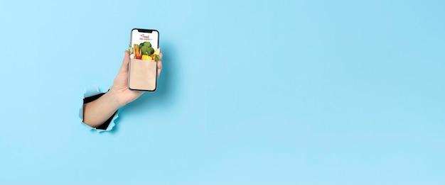 Frauenhand, die smartphone mit der online-bestellung der mobilen anwendung für die lebensmittellieferung im internet über blauem bannerhintergrund zeigt panoramabild