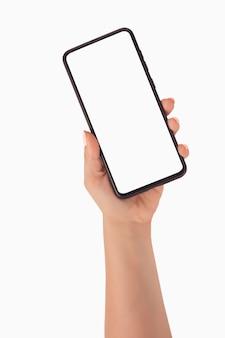 Frauenhand, die smartphone mit leerem bildschirm über weißem hintergrund verwendet auch im corel abgehobenen betrag. frauenhand, die den leeren bildschirm des schwarzen smartphones mit modernem rahmenlosem design hält, lokalisiert auf weißem hintergrund