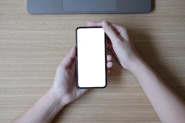 Frauenhand, die smartphone mit leerem weißen bildschirm am arbeitsplatz hält