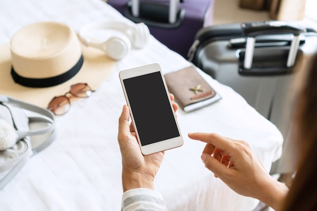 Frauenhand, die smartphone mit reiseaccessoires auf bett im hotelzimmer hält. reise-, entspannungs-, reise-, reise- und urlaubskonzepte. draufsicht und kopierraum.