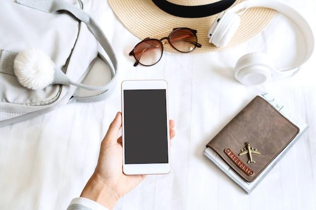 Frauenhand, die smartphone mit reiseaccessoires auf schlafzimmer hält