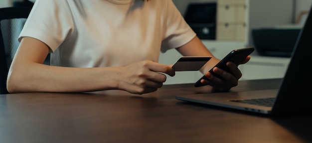 Frauenhand, die smartphone verwendet und kreditkarte mit zahlung online auf handy hält.