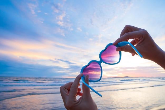 Frauenhand, die sonnenbrille in der herzform während des sonnenuntergangs hält.