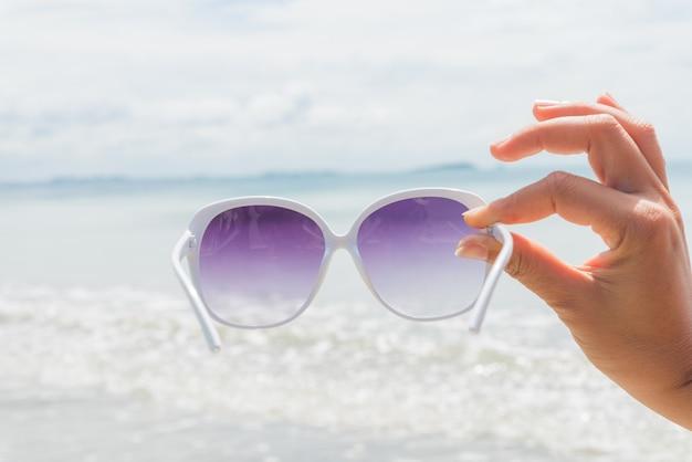 Frauenhand, die sonnenbrille über dem meer für sommerferienkonzept hält.