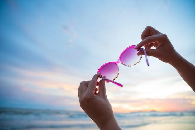 Frauenhand, die sonnenbrille über meer und sandigem strand während des sonnenuntergangs hält