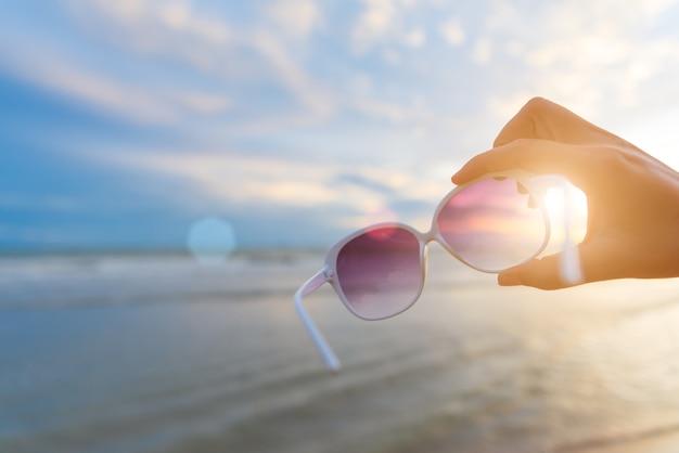 Frauenhand, die sonnenbrille über meer während des sonnenuntergangs für sommerkonzept hält.