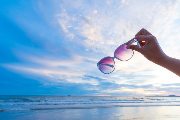 Frauenhand, die sonnenbrille über meer während des sonnenuntergangs hält