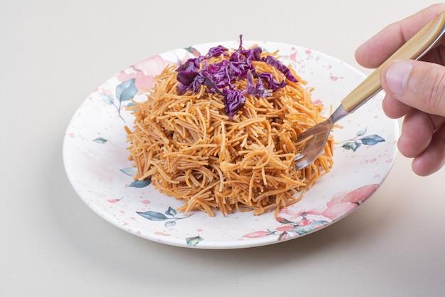 Frauenhand, die spaghetti vom teller mit gabel nimmt.