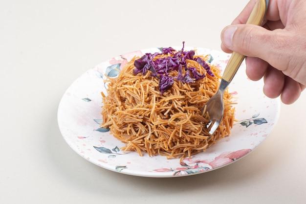 Frauenhand, die spaghetti vom teller mit gabel nimmt