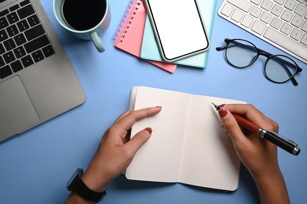 Frauenhand, die stiftschreiben auf notizbuch an ihrem arbeitsplatz hält.