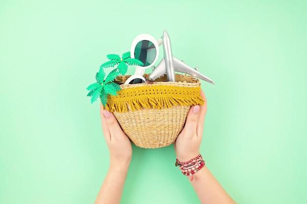 Frauenhand, die strohsack mit sommerferienzubehör hält. sommerferien, reisen in tropische länder, meer, sommerstil-konzept. draufsicht, flach liegen