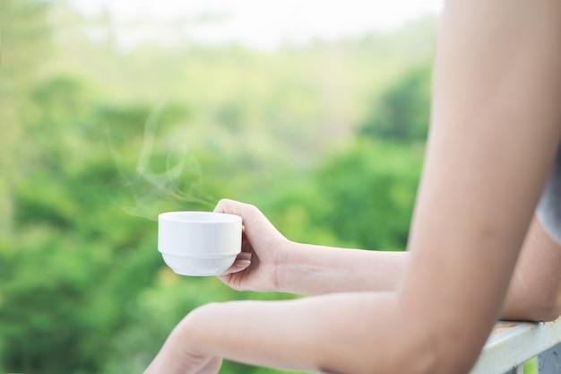 Frauenhand, die tasse heißen kaffee trinkt draußen hält