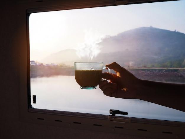 Frauenhand, die tasse heißen kaffees am morgen über glasfenster mit mountian-ansichtshintergrund hält.