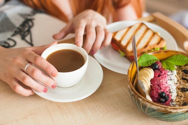 Frauenhand, die teeschale mit sandwich- und hafermehlfrühstück hält