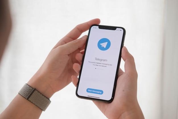 Frauenhand, die telefon mit sozialem netzwerkdienst hält