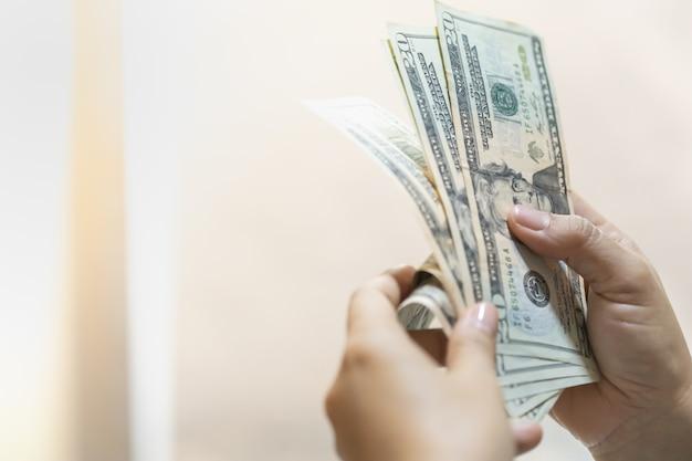 Frauenhand, die us-dollar banknote mit kopienraum hält und zählt.