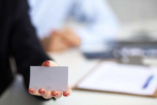 Frauenhand, die visitenkarte im büro gibt
