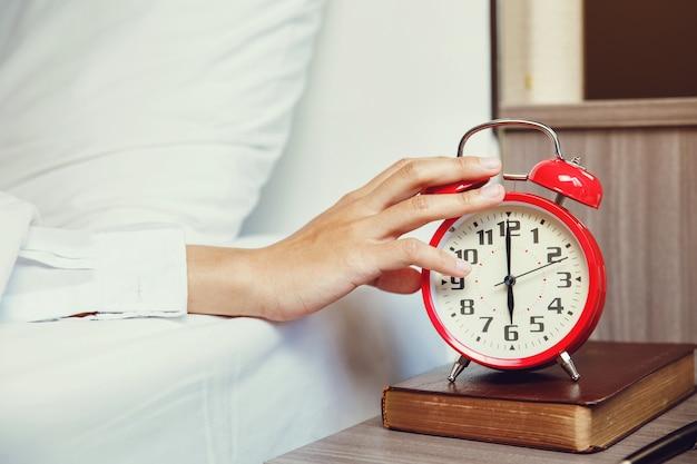 Frauenhand, die wecker abstellt, der am morgen aufwacht