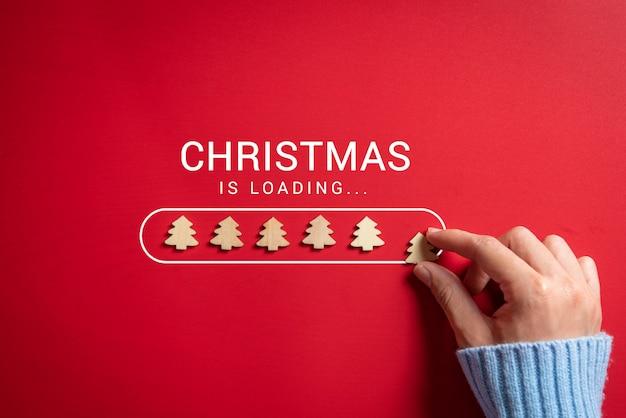 Frauenhand, die weihnachtsbaumikonenladestange auf das rot setzt