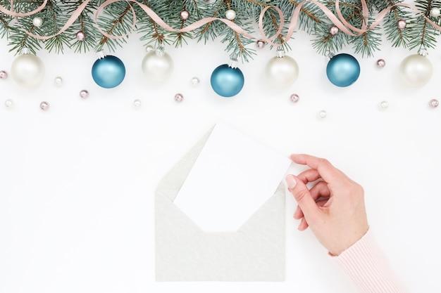Frauenhand, die weihnachtsgrußkarte hält