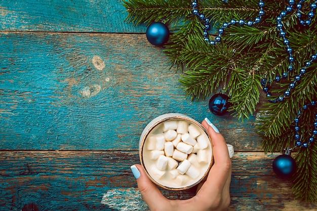 Frauenhand, die weihnachtsheißgetränk in einer tasse kakao mit marshmallow-schokoladenzimt und weihnachtsdekorationen auf einer hölzernen hintergrundoberansicht hält