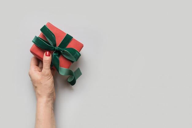 Frauenhand, die weihnachtsrotes giftbox mit grünem samtbogen hält.