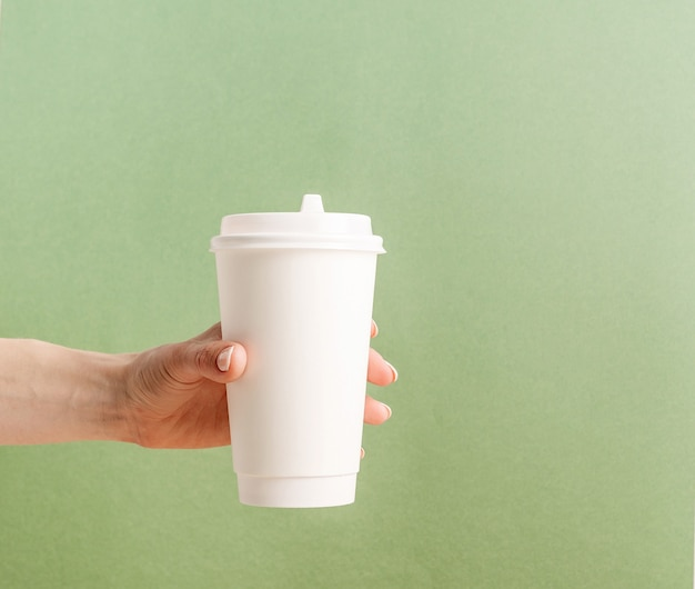 Frauenhand, die weiße große kaffeetasse papier zum mitnehmen papier auf grünem hintergrund hält