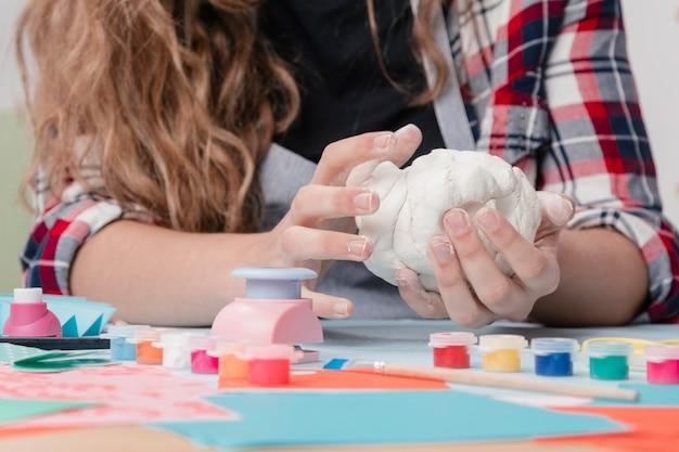 Frauenhand, die weißen lehm für handwerk knetet