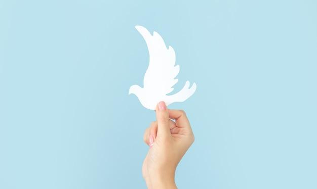 Frauenhand, die weißen papiertaubenvogel auf blauem hintergrund hält