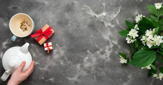 Frauenhand, die weißen teekanne trockenen tee jasminblütenbecher-geschenkgeschenkbox schwarzer weißer marmorhintergrund flach legt, hält