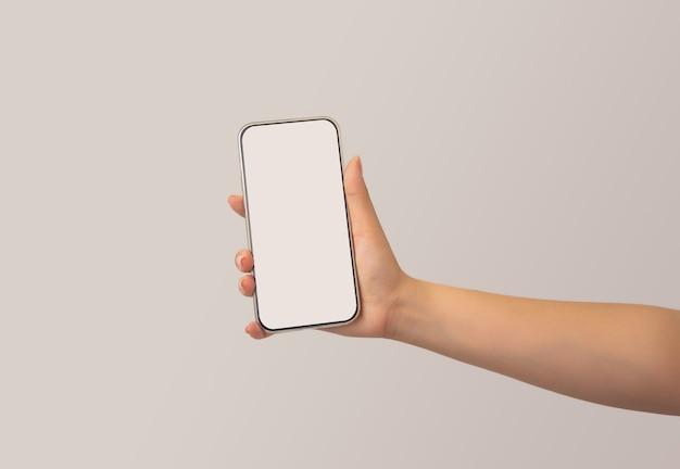 Frauenhand, die weißes intelligentes telefon mit leerzeichen der bildschirmanzeige, des intelligenten telefons und des modellkonzeptes, lokalisiert auf weißem hintergrund hält. selektiver fokus