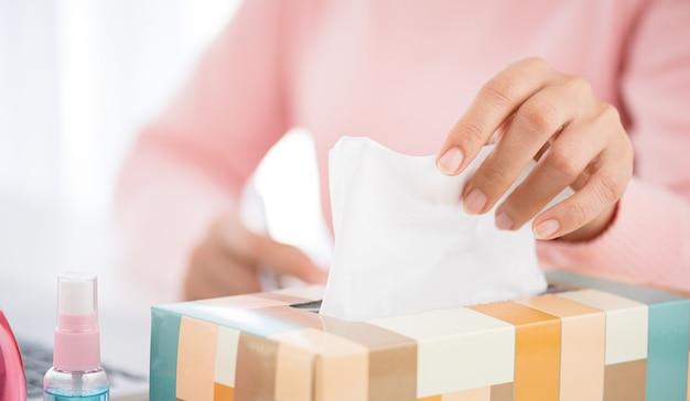 Frauenhand, die weißes seidenpapier mit desinfektionsgel und alkoholspray auswählt