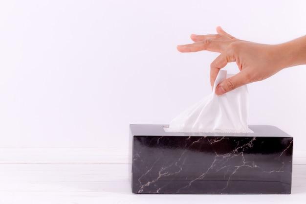 Frauenhand, die weißes seidenpapier vom gewebekasten auswählt.